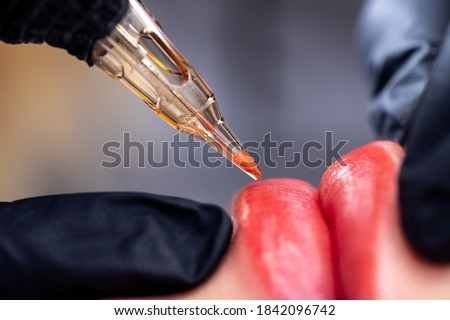 Macro photo of process of applying permanent makeup tattoo of red on lips woman.