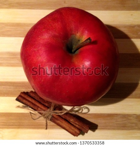 Macro photo of red apple and cinnamon sticks. Juicy red fruit apple and cinnamon lie on a wooden board.