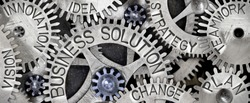 Macro photo of tooth wheel mechanism with BUSINESS SOLUTION, PLAN, STRATEGY, CHANGE, INNOVATION, VISION, TEAMWORK and IDEA words imprinted on metal surface