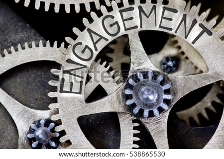Macro photo of tooth wheel mechanism with ENGAGEMENT concept letters