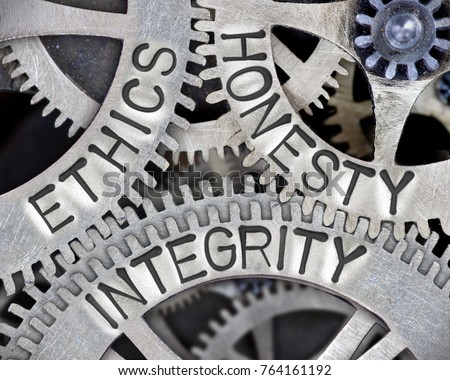 Macro photo of tooth wheel mechanism with ETHICS, HONESTY and INTEGRITY words imprinted on metal surface