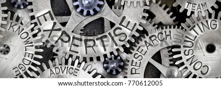 Macro photo of tooth wheel mechanism with EXPERTISE concept related words imprinted on metal surface #770612005