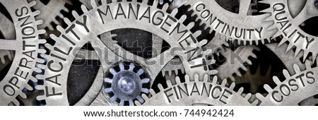 Macro photo of tooth wheel mechanism with FACILITY MANAGEMENT, OPERATIONS, FINANCE, COSTS, QUALITY and CONTINUITY words imprinted on metal surface