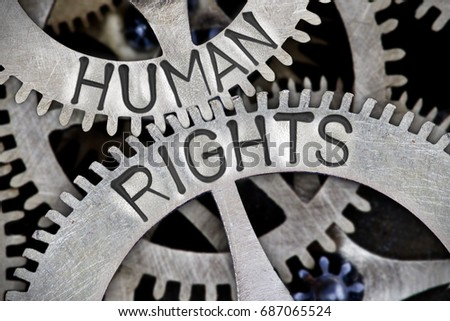 Macro photo of tooth wheel mechanism with HUMAN RIGHTS letters imprinted on metal surface #687065524