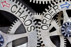 Macro photo of tooth wheel mechanism with imprinted arrows and CHAOS, ORDER concept words
