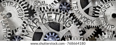 Macro photo of tooth wheel mechanism with MARKETING concept related words imprinted on metal surface