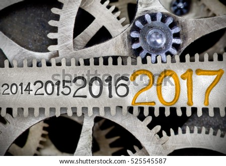 Macro photo of tooth wheel mechanism with numbers 2014, 2015, 2016, 2017 imprinted on clean metal surface; New Year concept #525545587