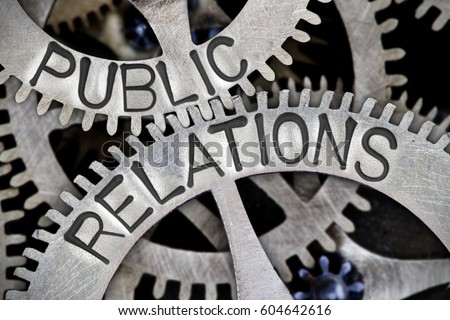 Macro photo of tooth wheel mechanism with PUBLIC RELATIONS letters imprinted on metal surface