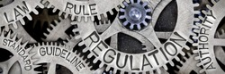 Macro photo of tooth wheel mechanism with REGULATION, LAW, RULE, AUTHORITY, GUIDELINE and STANDARD words imprinted on metal surface