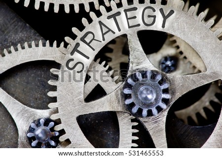 Macro photo of tooth wheel mechanism with STRATEGY concept letters