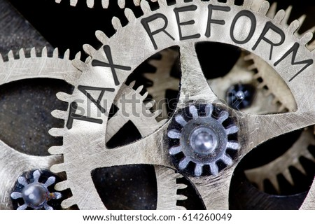 Macro photo of tooth wheel mechanism with TAX REFORM letters imprinted on metal surface