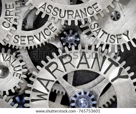 Macro photo of tooth wheel mechanism with WARRANTY concept related words imprinted on metal surface #765753601