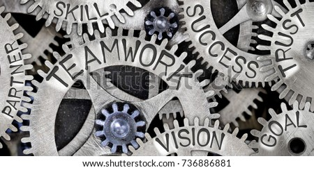 Macro photo of tooth wheels with TEAMWORK, SUCCESS, GOAL, VISION, TRUST, SKILL and PARTNER words imprinted on metal surface