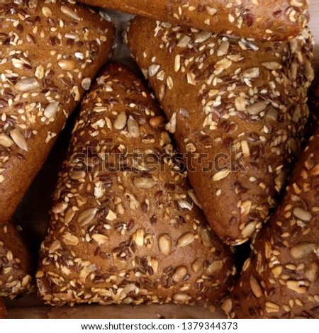 Macro Photograph of freshly baked bread. Bread in the form of triangular buns with sesame seeds and seeds. Fresh bread made from wholemeal flour.