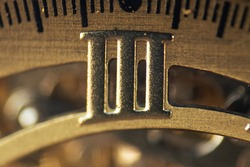 Macro photograph of the Roman numeral three on the inner dial of a bronze wristwatch. Conceptual image of time. Selective focus.