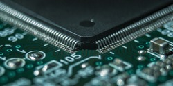 macro photography of integrated circuit in QFP package assembled on printed circuit board