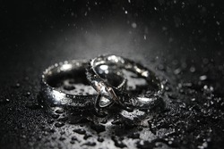 macro photography with two rings in splashes of water, drops falling over engagement rings symbolizing love, black and white photo with colorful shades