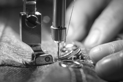 Macro shoot hand of the seamstress is using needle presser foot of industrial sewing machine for sew cloth or fabric with black and white tone (monochrome) close-up.