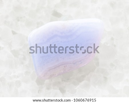 macro shooting of natural mineral rock specimen - polished blue lace agate (chalcedony, sapphirine) gemstone on white marble background #1060676915