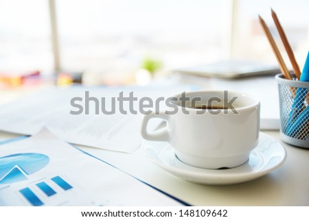 Macro shot of a coffee cup standing on the office desk