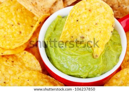 Macro shot of a corn chip dipped in fresh avocado guacamole dip.