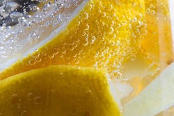 macro shot of a detail of detox water containing ginger and lemon with bubbles indicating freshness of the beverage