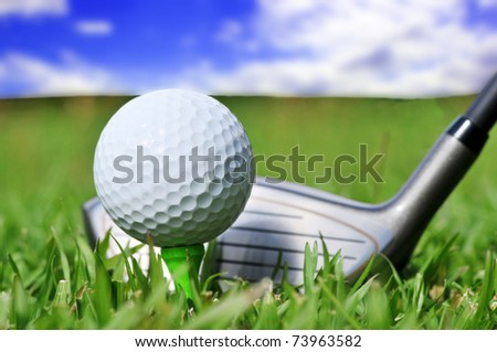 Macro shot of a golf club and ball with a beautiful blue sky in the background
