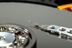 Macro shot of a magnetic needle on a hard disk platter, open HDD disk, perfectly clean surface.