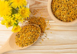 Macro shot of bee pollen or perga in wooden spoon on blurred rustic background. Raw brown, yellow, orange and blue flower pollen grains or bee bread. Healthy food supplement with selective focus