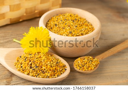 Macro shot of bee pollen or perga in wooden spoon on blurred rustic background. Raw brown, yellow, orange and blue flower pollen grains or bee bread. Healthy food supplement with selective focus Stock photo ©