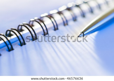 macro shot of business note-book with a pen in blue light