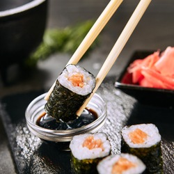 Macro shot of dipping salmon hosomaki sushi in soy sauce on natural black slate plate background with selective focus. Thin maki sushi rolls with raw trout, cucumber, rice, sesame and nori closeup