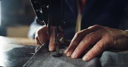 Macro shot of experienced tailor is sewing custom handmade high quality apparel in ancient luxury traditional tailoring workshop. Concept of industry, handmade, hand craft, couturier and tradition.