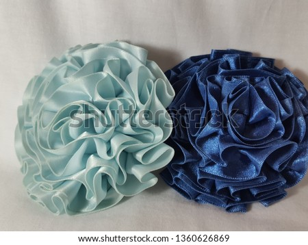 Macro shot of fabric rosettes sky blue and royal blue on a white background. The low lighting captures the texture of the satin fabric as well as the design of the accessories.  #1360626869