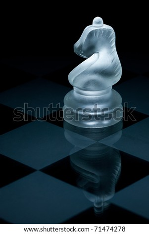 Macro shot of glass chess knight against a black background