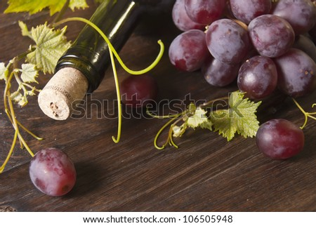 Macro shot of grapes and bottle of wine on wooden board. Background