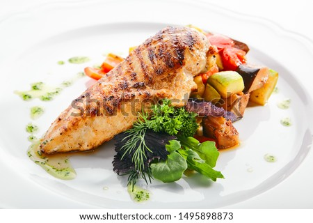 Macro shot of grilled chicken fillet with side dish of baked vegetables on white restaurant plate isolated. Bbq chicken breasts or white meat barbecue with fried zucchini and bell pepper closeup