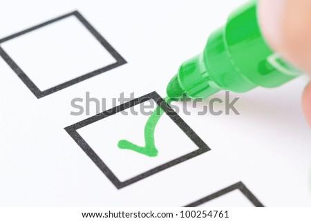 Macro shot of human hand drawing green check mark in checklist box