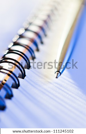 macro shot of pen and business note-book in blue light