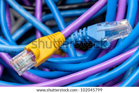 Macro shot of plugs on cat5e cables of many colors on top of tangle of wires