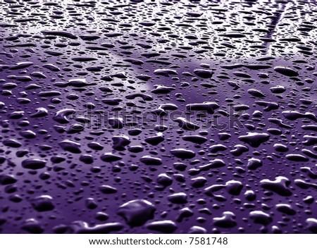 macro shot of rain drops on dark pink metallic surface