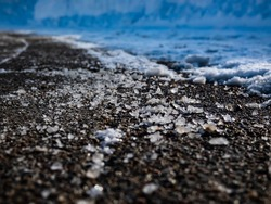 Macro shot of salt grains on icy sidewalk surface in the winter. Applying salt to keep roads clear and people safe in winter weather from ice or snow, closeup view