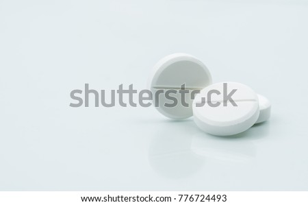 Macro shot of three white chewable tablets on white background with shadows. Antacids pills for relief stomachache from excess  gastric acid in stomach. Stress induce gastric ulcer treatment concept.