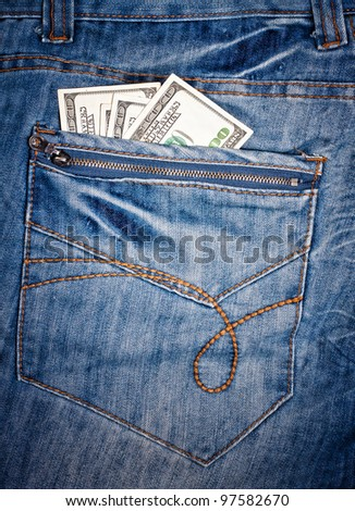 Macro shot of trendy jeans with american 100 dollars bills on its pocket