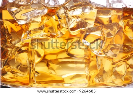 Macro Shot of Whiskey in Glass of Ice isolated over white