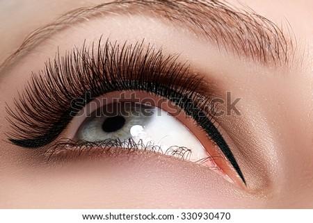 Macro shot of woman\'s beautiful eye with extremely long eyelashes. Sexy view, sensual look. Female eye with long eyelashes