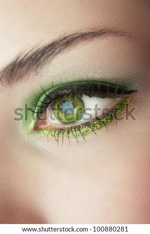 macro shot of woman's eye with green smoky eyeshadow and gold glitter .