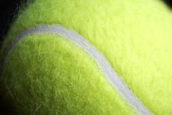 Macro shot of yellow tennis ball includes space for copy