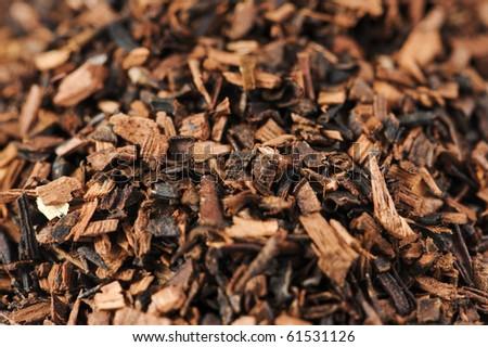 Macro studio shot of dry antioxidant rich healthy herbal rooibos tea - honeybush species - from the Western Cape region in South Africa.