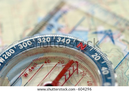 Macro view of a compass sitting on a topo map, sharp focus on the 'N'.